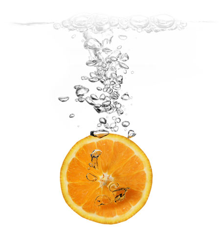 An orange slice being dropped in water to clean it.